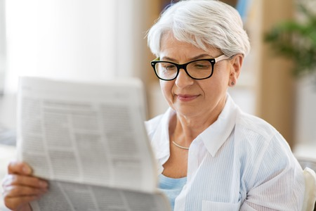 portrait of senior woman reading newspaper at home