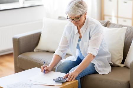 senior vrouw met papieren en rekenmachine thuis