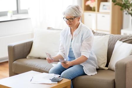senior woman counting money at home