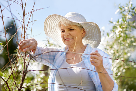 senior woman with garden pruner and flowers