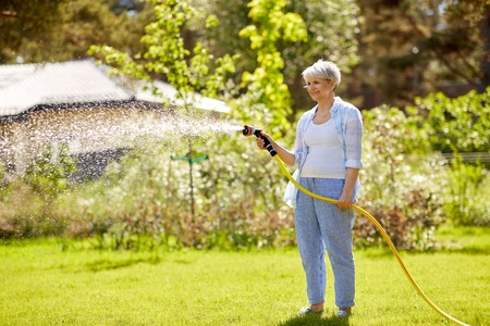 mujer mayor, regar, césped, por, manguera, en, jardín