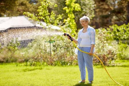senior vrouw gazon drenken door een slang in de tuin