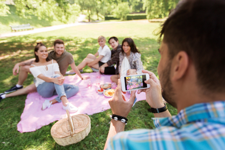 man photographing friends by smartphone at picnic