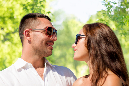 happy couple in sunglasses over green background