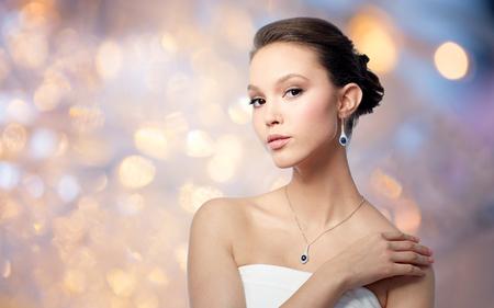 belle femme asiatique avec boucle d'oreille et pendentif