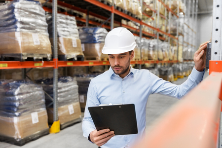 businessman in helmet with clipboard at warehouse Фото со стока