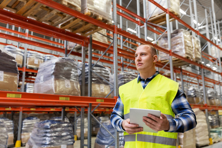 manual worker with tablet pc at warehouse