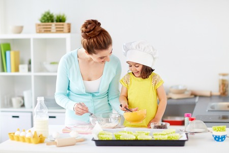 happy mother and daughter baking muffins at home Reklamní fotografie - 104316280