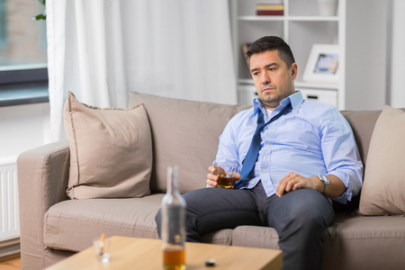 alcoholic with glass drinking whiskey at home