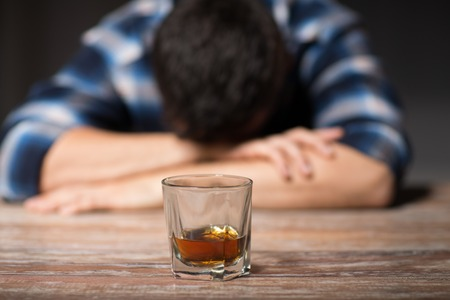 Hombre borracho con vaso de alcohol en la mesa por la noche Foto de archivo