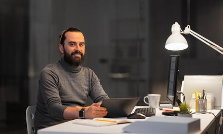 kreativer Mann mit Computer, der am Nachtbüro arbeitet Standard-Bild