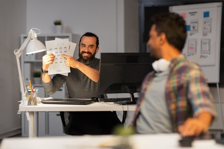 creative man showing papers to colleague at office