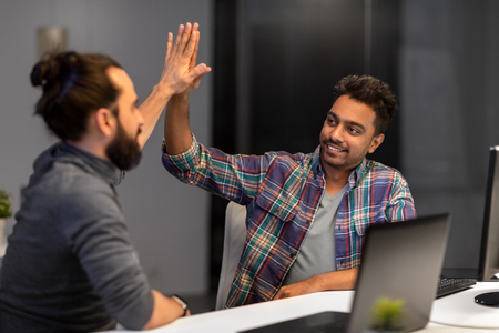 creative team making high five at night office Stock Photo