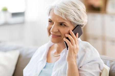 mujer mayor, llamar, en, teléfono inteligente, en casa