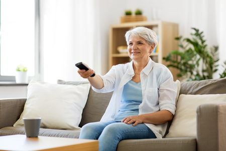 senior woman with remote watching tv at home