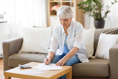 mujer mayor, con, papeles, y, calculadora, en casa