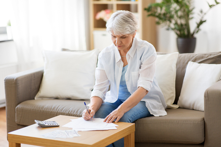 senior woman with papers and calculator at home Imagens - 104335898