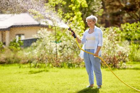 Mujer mayor regar el césped con una manguera en el jardín Foto de archivo
