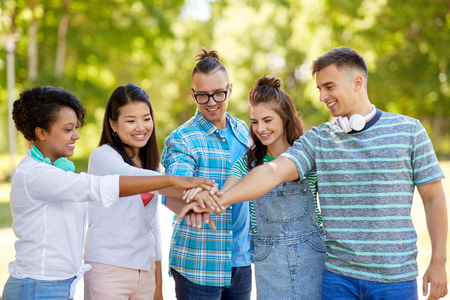 happy friends stacking hands in park