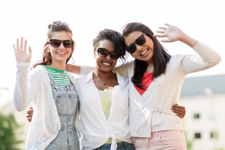 happy young women in sunglasses outdoors Stock Photo