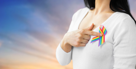 woman with gay pride awareness ribbon on her chest