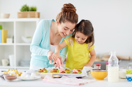 mother and daughter cooking cupcakes at home