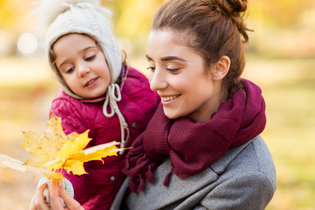 mother and little daughter with autumn leaves Stock Photo