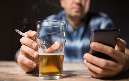 man with cellphone drinking alcohol and smoking
