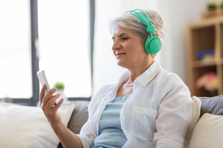 senior woman in headphones listening to music Stok Fotoğraf
