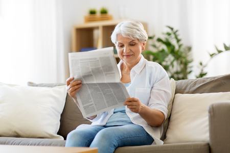 senior woman reading newspaper at home Banque d'images