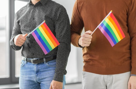 close up of male couple with pride flags