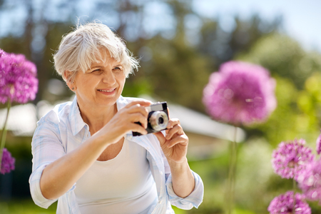 senior woman with camera photographing flowers