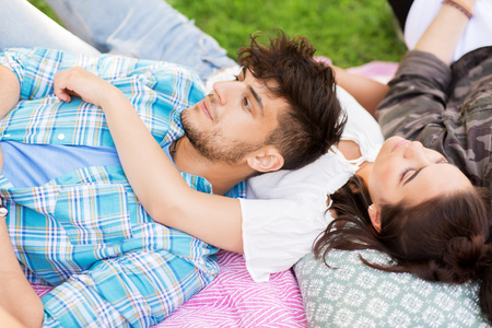 happy friends chilling on picnic blanket at summer Stock Photo