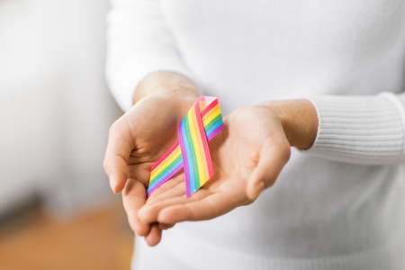 and concept - close up of female hands holding pride awareness ribbon