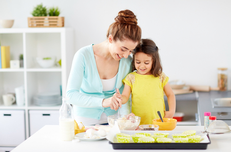 happy mother and daughter baking muffins at home
