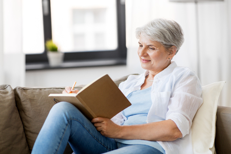 age, leisure and people concept - happy senior woman writing to notebook or diary at home Stockfoto