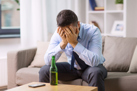 alcoholism, alcohol addiction and people concept - male alcoholic with bottle of beer at home