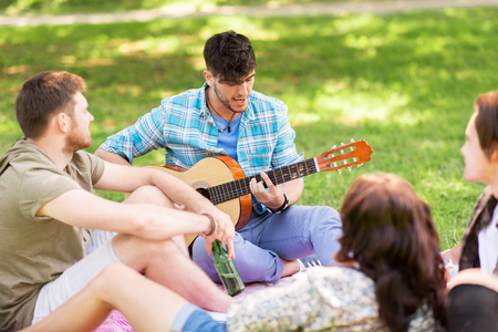 friends playing guitar at picnic in summer park Stock Photo