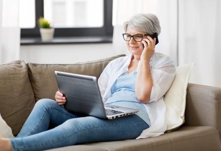 Technologie, Alter und Personenkonzept - glückliche ältere Frau in der Brille mit Laptop-Computer, der auf Smartphone zu Hause anruft
