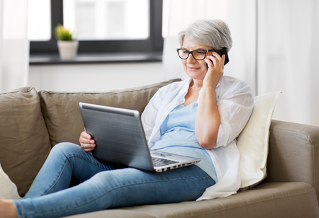 technology, old age and people concept - happy senior woman in glasses with laptop computer calling on smartphone at home
