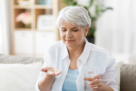age, medicine, healthcare and people concept - senior woman with glass of water taking pills at home