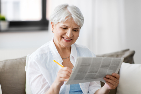 age and people concept - senior woman marking newspaper ad at home