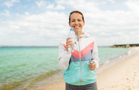 woman drinking water after exercising on beach