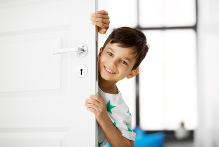 childhood, fun and people concept - happy little boy behind door at home