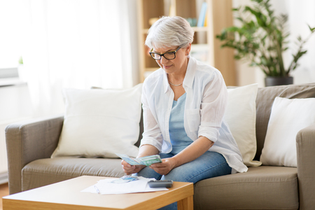 finances, savings, annuity insurance and people concept - senior woman with calculator and bills counting money at home Stock Photo