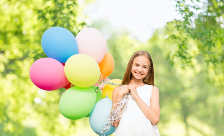 celebration, children and birthday party concept - happy girl with colorful balloons over green natural background Stock Photo