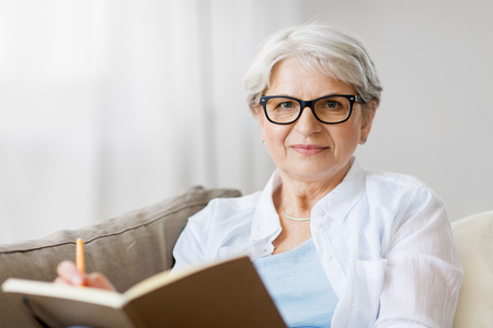 age, leisure and people concept - happy senior woman in glasses writing to notebook or diary at home