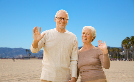 old age, travel and tourism and people concept - happy senior couple waving hands over venice beach background in california