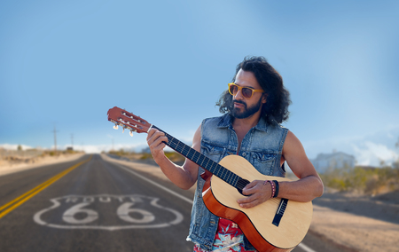music and people concept - hippie man playing guitar over us route 66 background Stockfoto