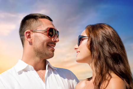 happy couple in sunglasses over sky background